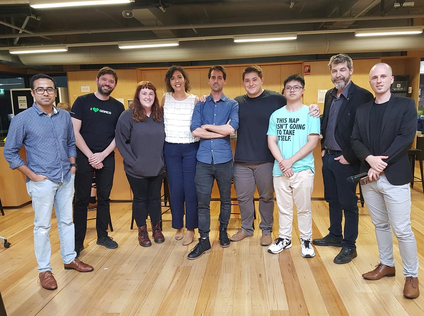 QUT alumni Lexi and Thomas and QUT student Daniel standing with the Queensland VR Hackathon organisers.